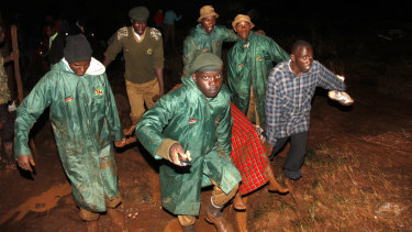 Members of the Kenya's National Youth Service carry away a dead body covered in a blanket during the early hours of Thursday.