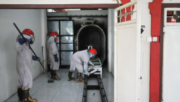 Workers check a cremation machine in Indonesia before cremating a COVID-19 victim.