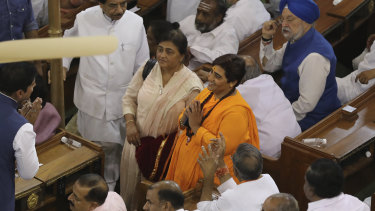 Elected lawmaker Pragya Singh Thakur, in orange dress, who is awaiting trial in connection with a 2008 explosion in Malegaon in western India that killed seven people, greets other lawmakers at an alliance meeting to elect Narendra Modi as their leader in New Delhi, India.