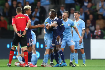 Victory's Adama Traore is held back by a City player after receiving his red card.