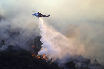 A helicopter drops water as the Getty fire burns in Mandeville Canyon.