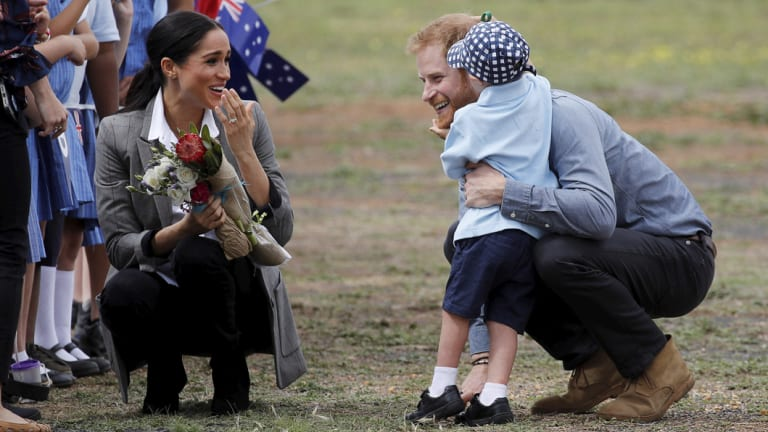 Britain's Prince Harry and Meghan, Duchess of Sussex are embraced by Luke Vincent, 5.