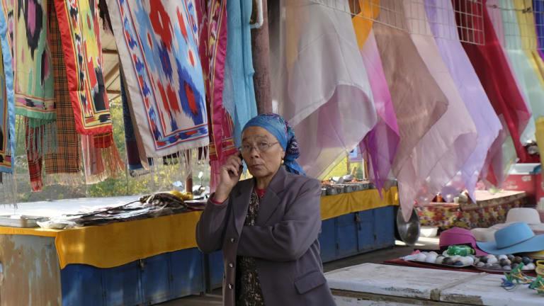 A souvenir vendor makes a call outside the Ermin Minaret in Turpan, Xinjiang.