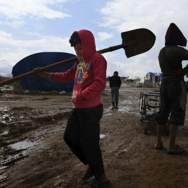 Children carry tools through the mud at the squalid al-Hawl camp.