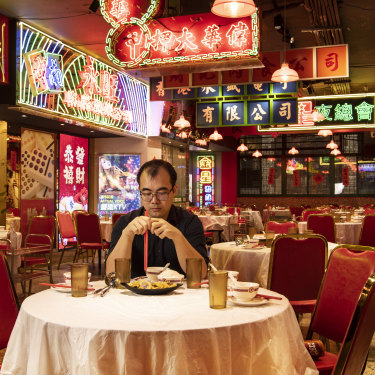 Good Luck Hotpot manager Jack Chen sits in his empty restaurant as the coronavirus crisis keeps people away.