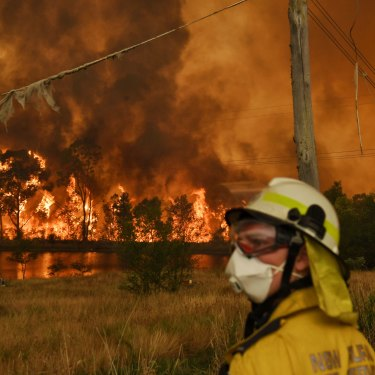 Members of the Rural Fire Service carefully watch the Gospers Mountain fire on the edge of The Fruit Bowl in Bilpin.