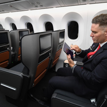 A cabin crew member takes a reaction test on an iPad onboard Qantas' long-haul test flight.