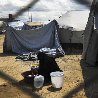 A woman washes clothes in front of her tent at the fence line of the Foreign section of al-Hawl camp in Syria.