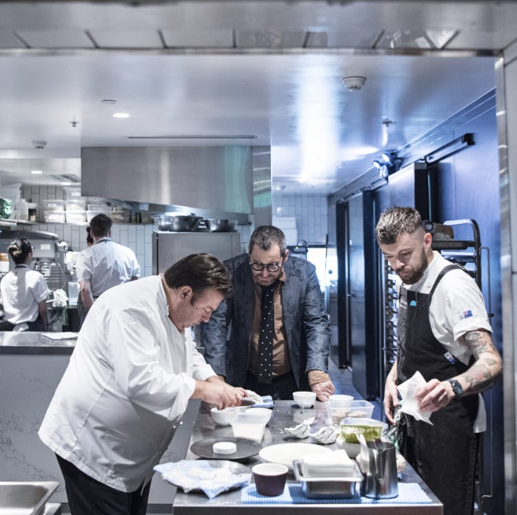 John Fink (centre) watches over as Peter Gilmore prepares a tasting menu for the new restaurant.