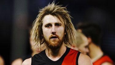 Dyson Heppell leads the Bombers from the field after their heavy loss to the Bulldogs.