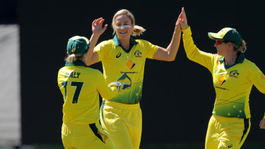 Ellyse Perry celebrates a wicket with Alyssa Healy (left) and Meg Lanning (right).