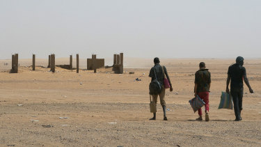 Three men head north towards Algeria after crossing the Assamaka border post in northern Niger on June 3.