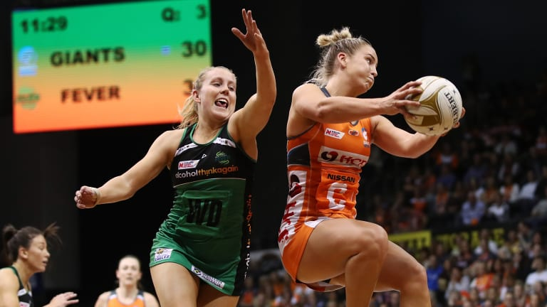 Human shield: Jamie-Lee Price of the Giants contests for the ball against Jessica Anstiss of the Fever.