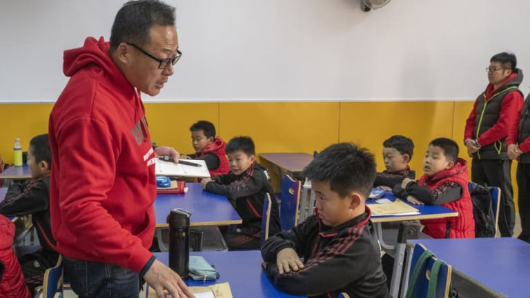"""Tang Haiyan, founder of the Real Boys Club, lectures a student. """"We will never cultivate sissies,"""" he says."""