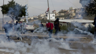 Palestinian demonstrators run from tear gas fired by Israeli troops during clashes after a demonstration  at Hawara checkpoint near the West Bank city of Nablus, on Sunday.