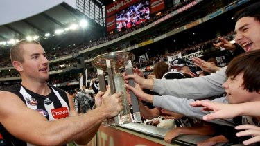 Magic moment: Magpies ruckman Darren Jolly takes the 2012 trophy to the Collingwood cheersquad.