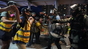 Church volunteers wearing vests that say 'protect the children' block policemen who arrived at Tung Chung to arrest protesters.