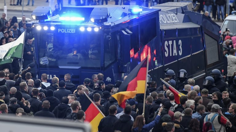 A police water cannon stands between far-right demonstrators in Chemnitz, eastern Germany, on Saturday.