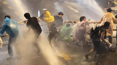 Protesters are hit with water canons as police try to clear an area in Bangkok on Friday, October 16.