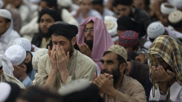 Supporters of Pakistani religious party Jamiat Ulema-e-Islam pray during a rally to condemn Asia Bibi's acquittal.
