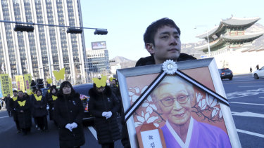 A mourner carries a portrait of the deceased Kim Bok-dong, during her funeral ceremony in Seoul on Friday.