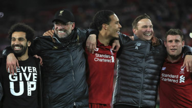 Jurgen Klopp (second from left) celebrates Liverpool's win with his players and staff.