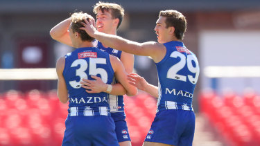 Charlie Lazzaro celebrates a goal with his North Melbourne teammates.