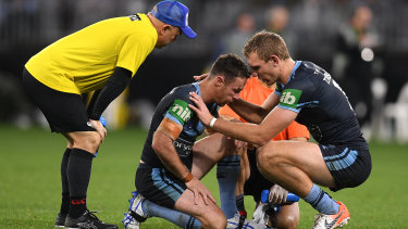 Focus of attention: James Maloney receives treatment. He took some late hits as the price to pay for a commanding performance.