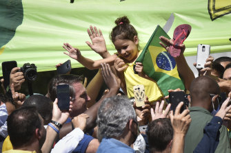 "Brazil's President Jair Bolsonaro, left of girl, greets supporters outside the presidential palace in Brasilia, during a daily ""door stop""."