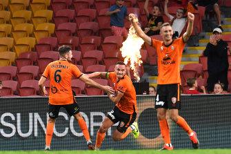 Tom Aldred of the Roar, centre, celebrates scoring a goal in round 18.
