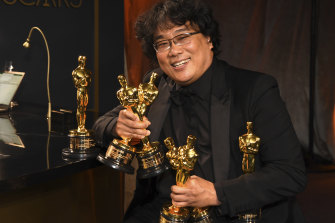 Bong Joon-ho holds the Oscars for best original screenplay, best international feature film, best directing and best picture.