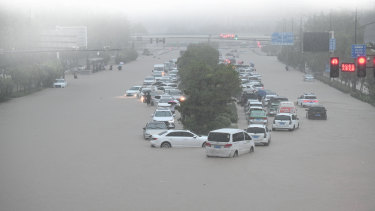Vehicles are stranded in floodwater near Zhengzhou Railway Station on July 20. Floods in China and Germany have hampered global supply chains.