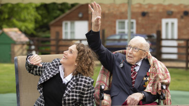 Colonel Tom Moore and his daughter Hannah wave as a Spitfire and a Hurricane pass over his home to celebrate the veteran's 100th birthday.