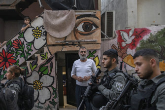 Israeli police officers walk past Nasser Rajabi as he stands outside the house that he shares with Jewish settlers in East Jerusalem.