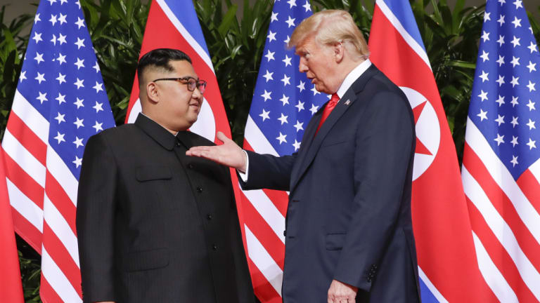 US President Donald Trump gestures towards the meeting site with North Korea leader Kim Jong-un at the Capella resort on Sentosa Island, Singapore.