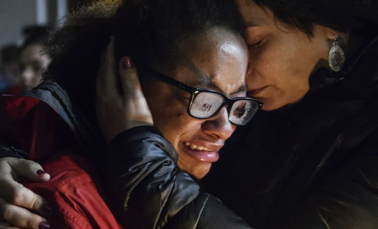 Isabel Kinnane Smith is comforted by Lesley Britton at a vigil for the victims of the Tree of Life synagogue shooting.
