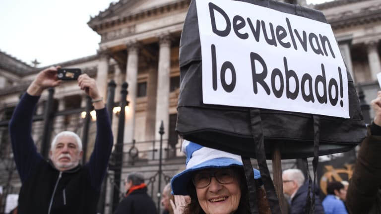 "A demonstrator holds up the Spanish message: ""Give back what was stolen!"" during a march against former president Cristina Kirchner in Buenos Aires."