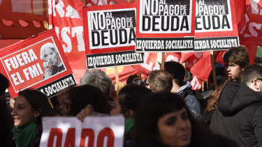 """Protesters hold signs that read in Spanish: """"Out IMF and No to the payment of the debt"""" during a demonstration against the IMF near a G20 Finance Ministers meeting in Buenos Aires, Argentina, in July."""