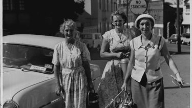 """Here come the """"angels"""" from left, Mrs. Gould, Mr. Jobling, Mrs. Henderson delivering meals in the South Sydney area. March 20, 1958."""
