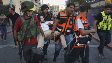 Israeli security forces and paramedics carry a wounded Jewish man after he was shot during violent unrest in Lod on Thursday.