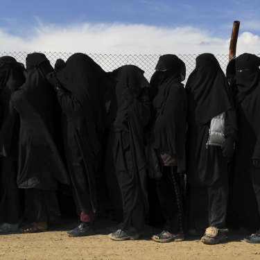 Foreign IS wives and children line up near the foreign section of al-Hawl camp to be taken to the shops.