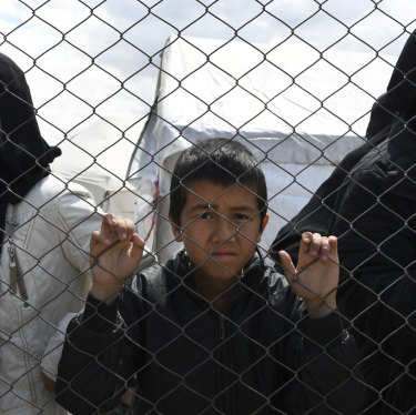 Foreign ISIS wives and children at the fence line of the Foreign section of al-Hawl camp.