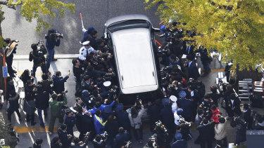 "A car carrying ""Twitter Killer"" Takahiro Shiraishi leaves a Tokyo police station in November."