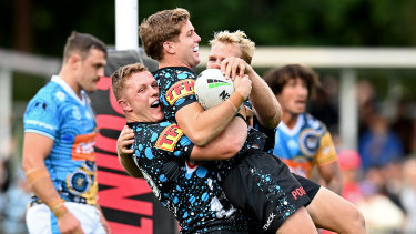 Blayke Brailey scores for the Sharks and is mobbed by teammates at Coffs International Stadium.