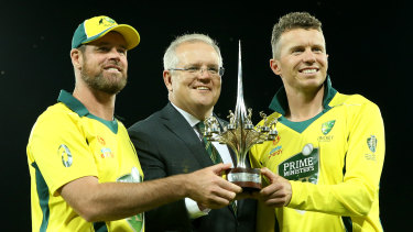 Prime Minister Scott Morrison holds the trophy with Dan Christian and Peter Siddle.