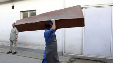 An Afghan man carries an empty coffin in the hospital following a deadly attack outside the Rural Rehabilitation and Development Ministry in Kabul, Afghanistan, on Sunday.