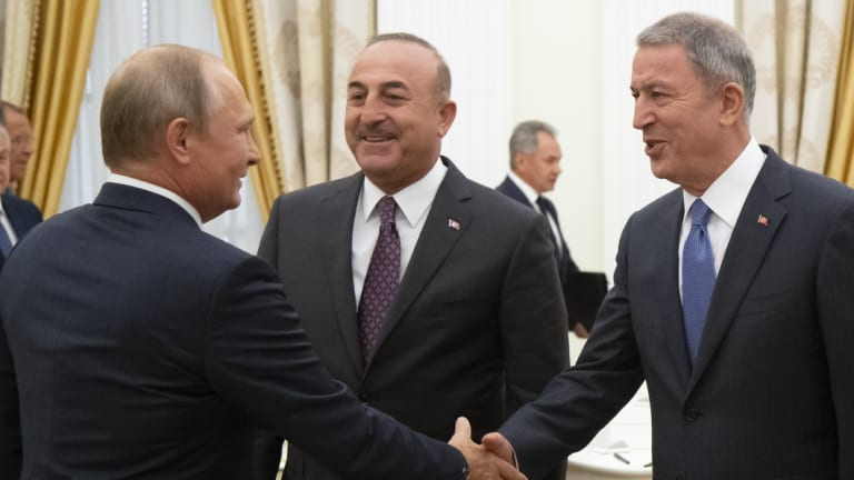 Russian President Vladimir Putin, left, greets Turkish Foreign Minister Mevlut Cavusoglu, centre, Turkish Defence Minister Hulusi Akar, during their meeting in the Kremlin in Moscow, Russia, on Friday.