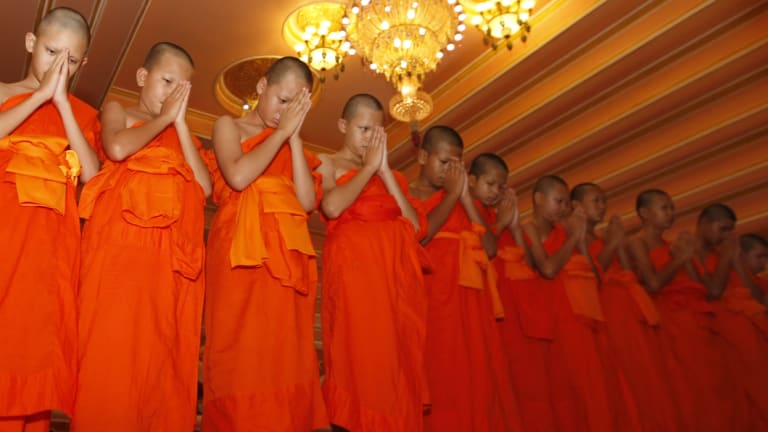 Members of Wild Boars soccer team pray during a ceremony marking the completion of their serving as novice Buddhist monks.