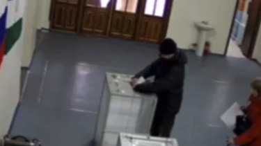In this screen grab taken from video provide by the Central Election Commision  via Navalny Opposition Group on Sunday,  a man allegedly stuffs ballots into a ballot box at a polling station.