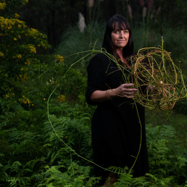 """Sydney fibre artist Catriona Pollard in the bush surrounding her studio. She says weaving is """"about letting the material speak""""."""